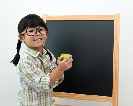 Little Asian girl holding a green apple and smile in front blackboard photo