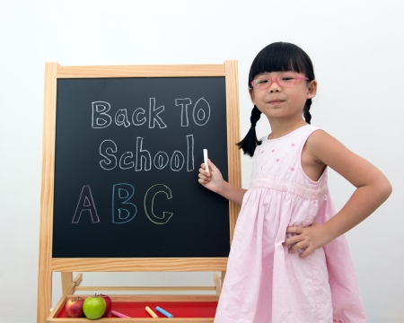Little Asian girl in front of the blackboard pointing back to school