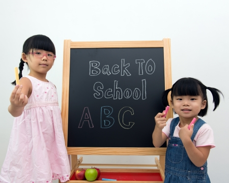 Kids holding chalks standing in front of the blackboard photo