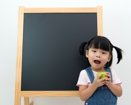 Portrait of little girl holding apple in front of the blackboard photo
