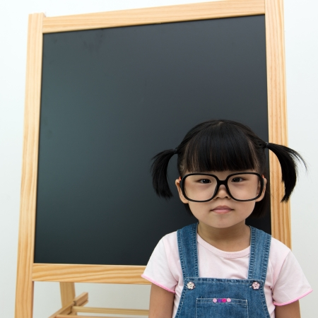 Little Asian child with big spectacles in front blackboard