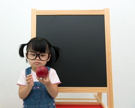 Portrait of little girl holding apple posing in front of the blackboard photo
