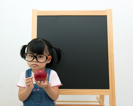 Portrait of little girl holding apple posing in front of the blackboard photo