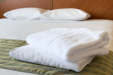 accomodation: White clean towels stacked on the hotel bed Stock Photo