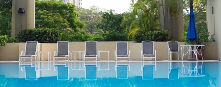 loungers: Luxury resort hotel swimming pool with sun loungers Editorial