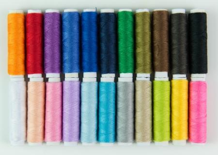 Close-up image of colourful bobbins isolated on white background