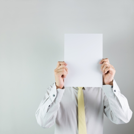 Man holding blank whiite board on his face over white background photo