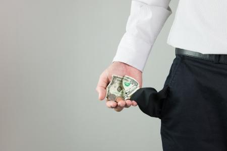 bolsa dinero: Hombre que muestra el poco de dinero que queda en el bolsillo