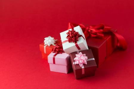 three gift boxes: Tres cajas de regalo envuelto con cintas y arco aislado sobre fondo rojo