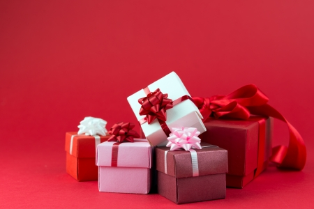 birthday gift: Three gift boxes wrapped with ribbons and bow isolated over red background