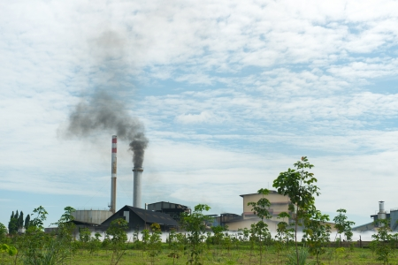 polluting: Factory chimney polluting air with dark smoke Stock Photo