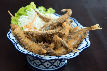 Deep fried anchovies with salad over black background