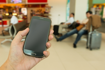 device: Close up of hand holding smartphone at airport
