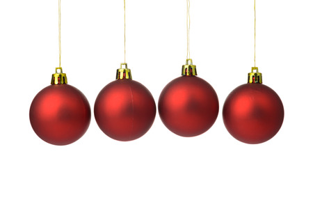 Red Christmas balls hanging on string over white background