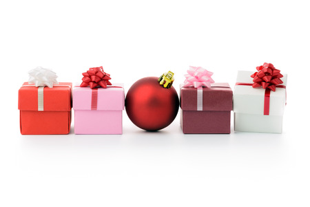 Multi color gift boxes and Christmas bauble in a row photo
