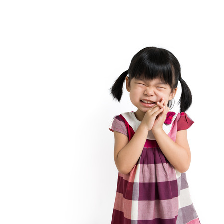 squeeze: Portrait of little Asian girl squeezing her eyes
