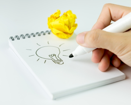 Concept of idea with hand drawn light bulb on notebook photo
