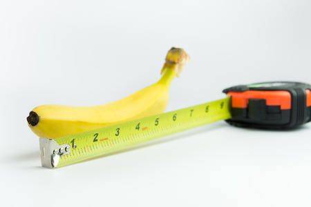 Close-up of measuring the size of banana on white background Archivio Fotografico