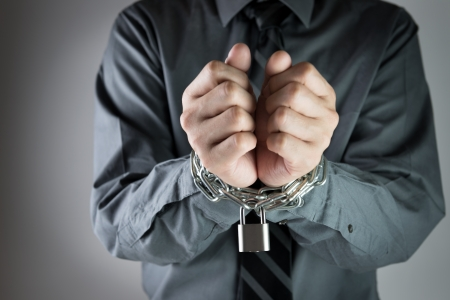 Close-up of businessman with chained hand on black background photo