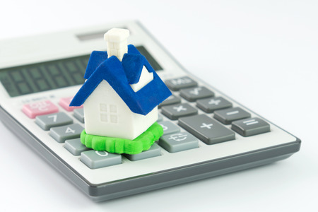 Miniature house model with calculator isolated on white background photo