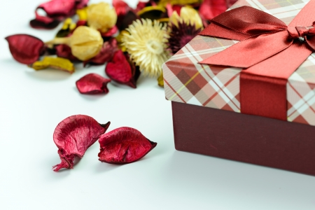 Gift box and dried petals on white background photo