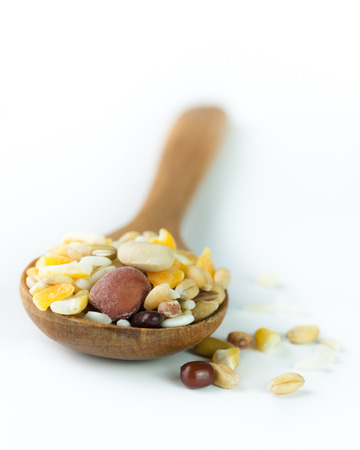 Mixed healthy grains on wooden spoon over white background photo