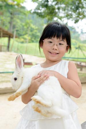 asian bunny: Portrait of Asian toddler girl holding white rabbit Stock Photo