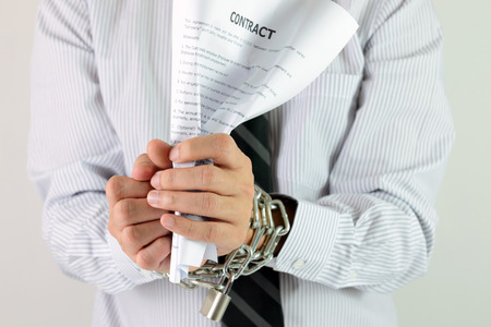 slave labor: Businessman hands with tied with chains and hold contract Stock Photo