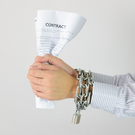 enslaved: Businessman hands with tied with chains and hold contract Stock Photo
