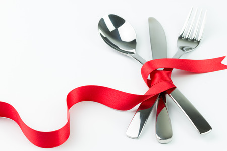 Fork, spoon and knife tied up with red ribbon isolated on white background photo