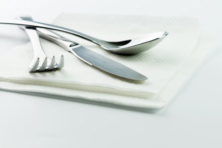 Stainless steel fork, knife and spoon with paper napkin