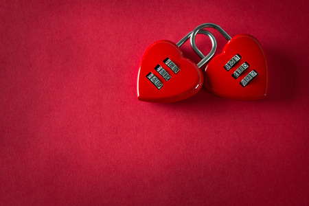 Two love combination padlock bonded together in red background photo