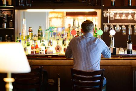 hombre tomando cerveza: Hombre solo en camisa, sentado en el escritorio bar