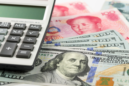 US one hundred dollar and China Yuan bills with calculator