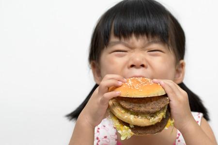comida chatarra: Niña con gran hamburguesa o un sandwich dentro de la boca Foto de archivo