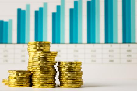 fondos negocios: Las pilas de monedas de oro con la carta financiera Foto de archivo
