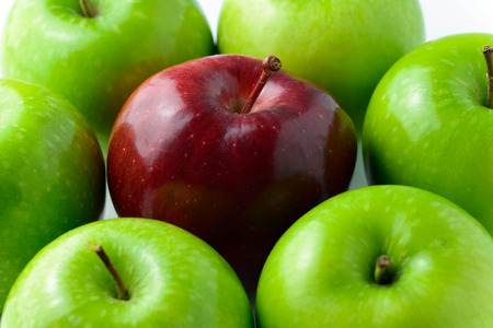 outstanding: Red apple in the middle of green apples for outstanding conceptual Stock Photo