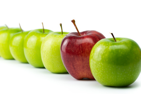 distinctive: Red apple standing out in a row of green apples
