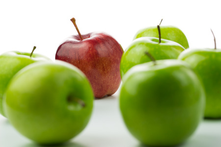 distinctive: Red apple standing out among green apples