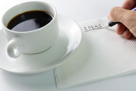 pensamiento estrategico: Lluvia de ideas con ideas escritas en una servilleta con la pluma y la taza de café