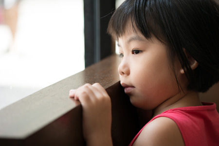 Sad Asian little child looking outside of window Stock Photo