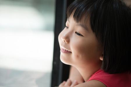 Sad Asian little child looking outside of window photo