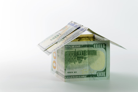 refinance: Close up of miniature house build with US dollar