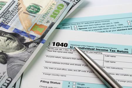 filing documents: Filling out income tax forms with US dollar and pen