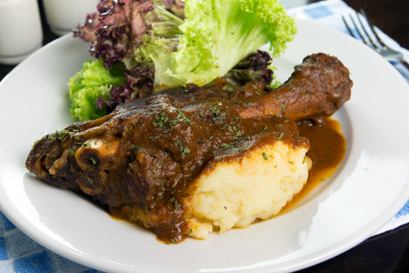 Braised lamb shank with mashed potato and salad served on white plate photo