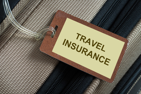 Travel insurance tag tied to a luggage photo