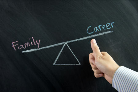 Thumb up in front of career and family balance drawn on chalkboard photo