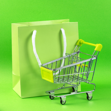 Close up of green shopping cart and gift bag photo
