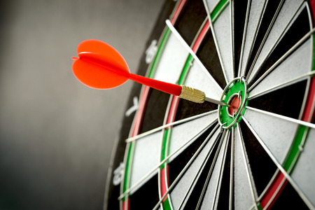 target: Right on target concept using dart in the bullseye on dartboard Stock Photo