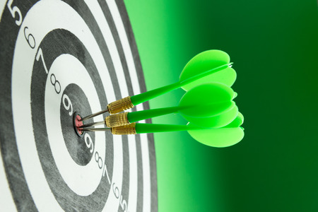 Three green darts pinned right on the center of dartboard